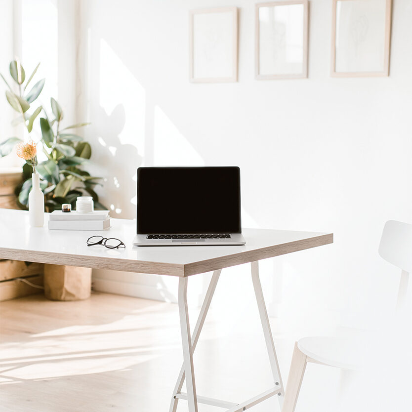 a white desk and a laptop